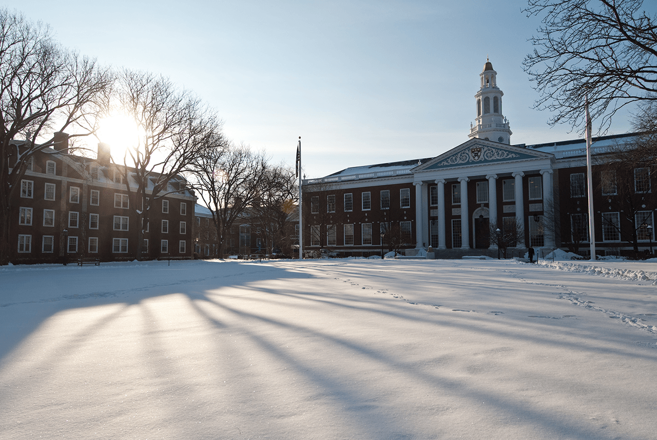 The winter afternoon sun casts shadows on the lawn of Baker Library on the Harvard Business School campus.