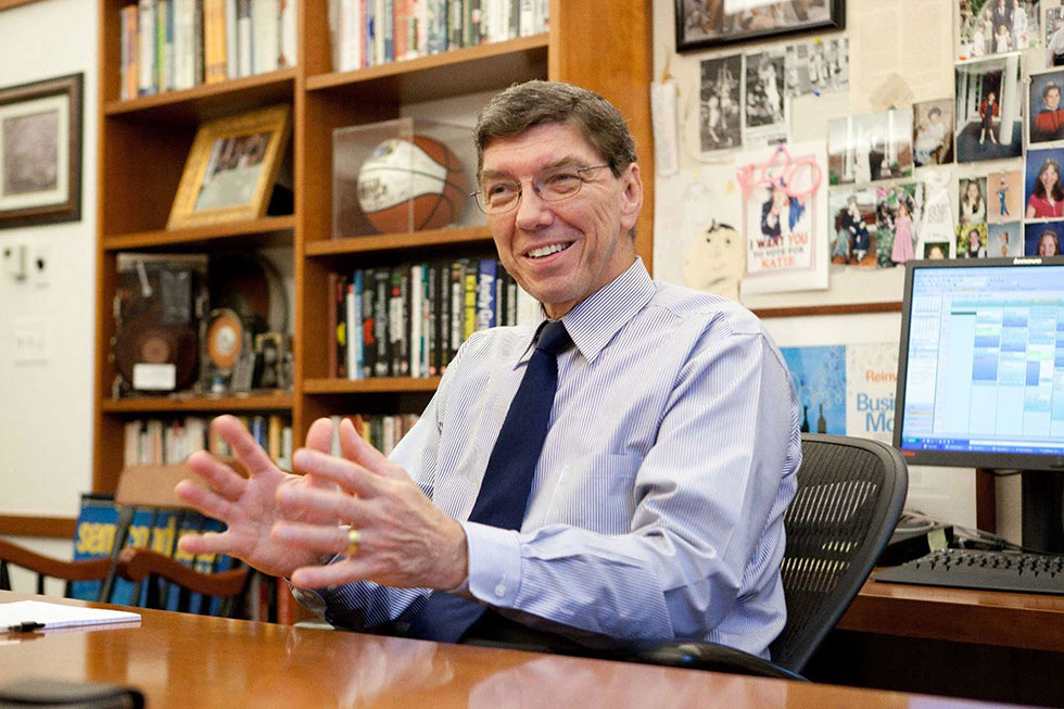Clayton Christensen sitting at his desk